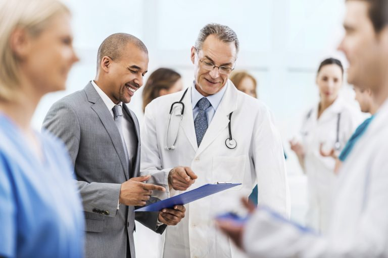 Mature doctor and African American businessman looking at documents. There are people around them.
