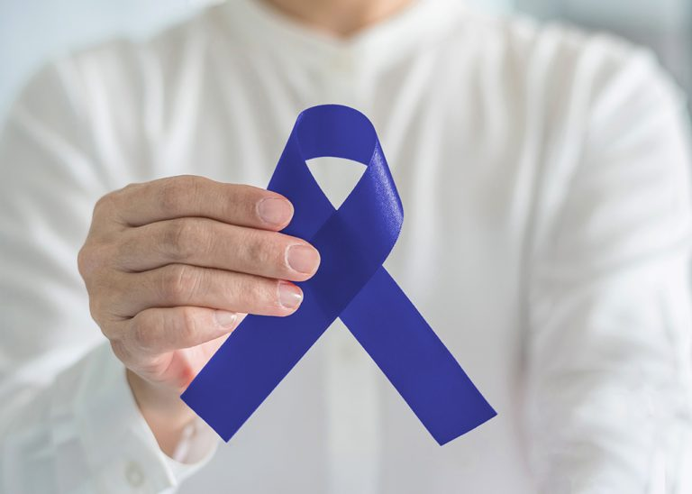 Colorectal Colon cancer awareness ribbon for men's health care concept with blue bow color in person's hand